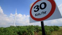 30 km/hr traffic sign , wind turbines background, Dolly slide shot. Stock Footage