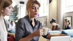 Business women meeting in cafe using laptop drinking coffee Stock Footage