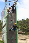 abseiling on climbing wall in banos, ecuador - stock photo