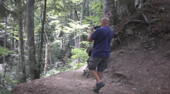 HD. Tourist walking on a trail in the woods and shooting beautiful landscape. Stock Footage