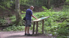 HD. Tourist looking to a map in the forest. Tourist searching a new trail. Stock Footage