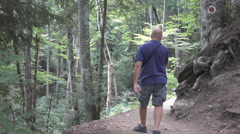 HD. Tourist walking on a trail in the woods shooting beautiful landscapes. - stock footage