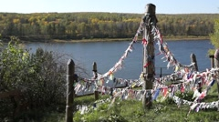 Pagan colorful cloth for spirits on the cliff over river - stock footage