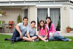 Stock Photo of happy family relaxing in backyard of new home