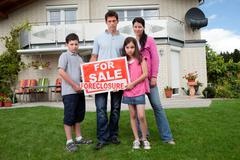 Young family holding a foreclosure sign Kuvituskuvat