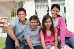 beautiful young famliy of four sitting together - stock photo