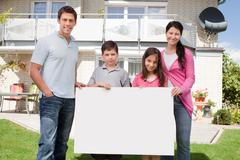 Stock Photo of young family holding a black white board