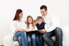 Hapy young family watching photo album Stock Photos