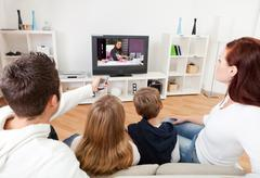 Young family watching tv at home Stock Photos