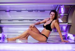 Young woman posing on tanning bed Stock Photos