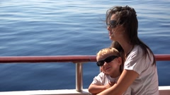 Attractive mother holding lovely baby child in her arms , cruise, blue sea  Arkistovideo