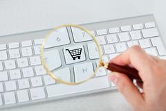 looking at shopping basket key through magnifying glass - stock photo