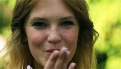 Young girl sending kiss and smiling to the camera in the park, steadycam shot Stock Footage
