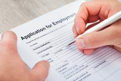 Close-up of hand filling application for employment Stock Photos