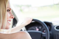 female hand holding steering wheel - stock photo