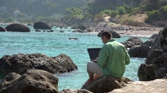 Man sitting on rocky seashore, laptop, successful deal happy rising up hands 4k Stock Footage