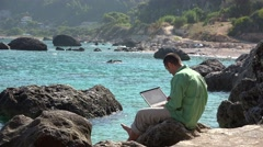 Man with a laptop on rocky seashore, beautiful sea waving view 4K Stock Footage