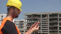 Plumber outside construction site, checking tapes functionality cute man working Stock Footage
