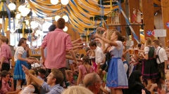 MUNICH BEER FESTIVAL Oktoberfest Octoberfest people drinking dancing on table in Stock Footage