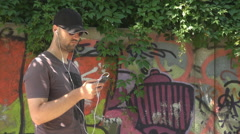 Stylish model boy listening music at smartphone, earphones on, graffiti art wall Stock Footage