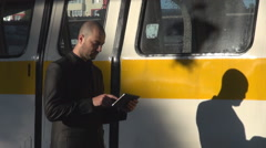 PAN shot handsome white commuter working on tablet in train station subway wagon Stock Footage