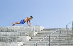 Man doing Push-ups on Bleachers, Miami Beach, Florida, USA - stock photo