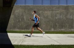 Man Running on Sidewalk - stock photo