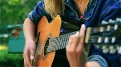 Teeange girl playing on the guitar in the park, steadycam shot Stock Footage