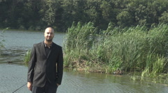 Suit and tie businessman outdoor, portrait of young man in nature wild lake view Stock Footage