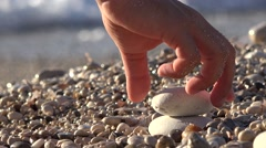 Hand arranging little withe stones in pyramid shape, sea waving beach shore 4k Stock Footage