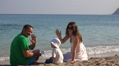 Adorable child and parents sitting on seashore, waving hands, hello, good bye  Stock Footage