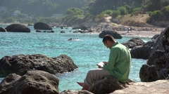 Young man with a touch pad sitting on rocky seashore, relaxing view  Stock Footage