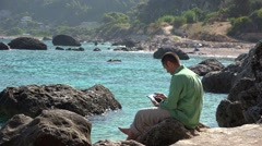 Man using a tablet computer, beautiful seaside landscape  Stock Footage