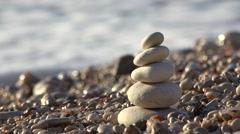 Little stones in pyramid shape, sea waving on beach stones  Stock Footage