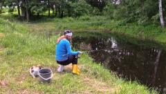 Blond pregnant woman catch fish on pond shore with cute cat Stock Footage