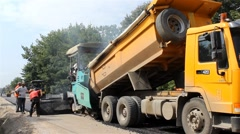 Truck pouring asphalt in machine for paving,roller flatten behind by Pakito. Stock Footage