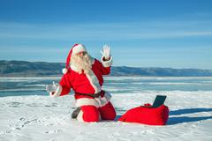 santa claus sitting on snow, looking at laptop news - stock photo