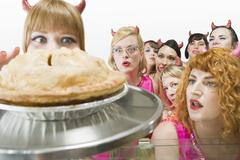 Women Wearing Devil Horns Looking at Apple Pie Stock Photos