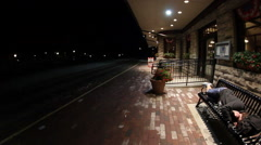 Pan left to right of woman sleeping on train station bench Stock Footage