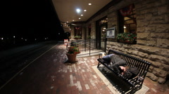 Woman sleeping on bench at train station Stock Footage