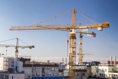 Construction site with tower cranes against clear sky. Stock Photos