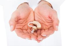 close-up of a person holding hearing aid in cupped hands - stock photo