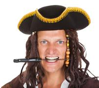 Pirate holding knife in his mouth Stock Photos