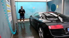 Cleaning a vehicle in a self-service car wash Stock Footage