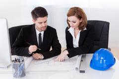 portrait of two sincere architects working in office - stock photo