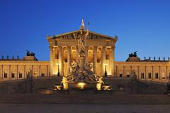 Austrian Parliament and Pallas Athene statue in Vienna illuminated at dusk. Stock Photos