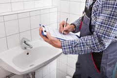 close-up of plumber standing in front of washbasin writing on clipboard - stock photo