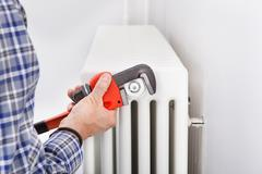 Plumber fixing radiator Stock Photos