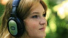 Happy girl relaxing and listening music on headphones, steadycam shot Stock Footage