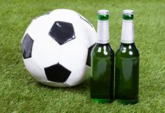 Close-up of soccer ball and beer bottles on green grass Stock Photos